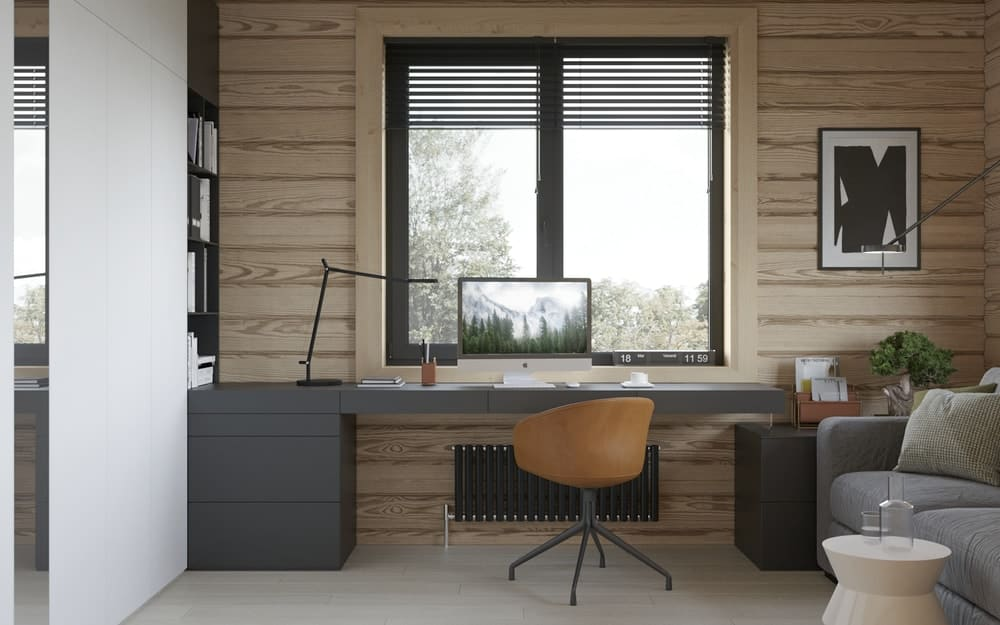 This is a simple office with a modern black desk with built-in drawers and shelves on the side that contrast the white wall beside it.