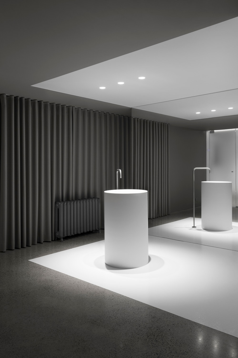 This angled view of the powder room shows the pedestal sink standing in the middle of the white floor bordered with dark tiles and dark gray curtains.
