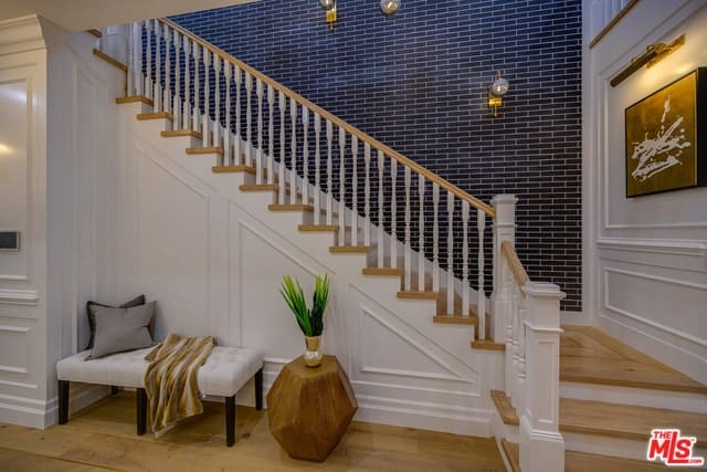 This simple foyer has a black patterned wall on its staircase that gives a nice contrast to the bright and white elements of the foyer along with the legs of the cushioned bench at the side.