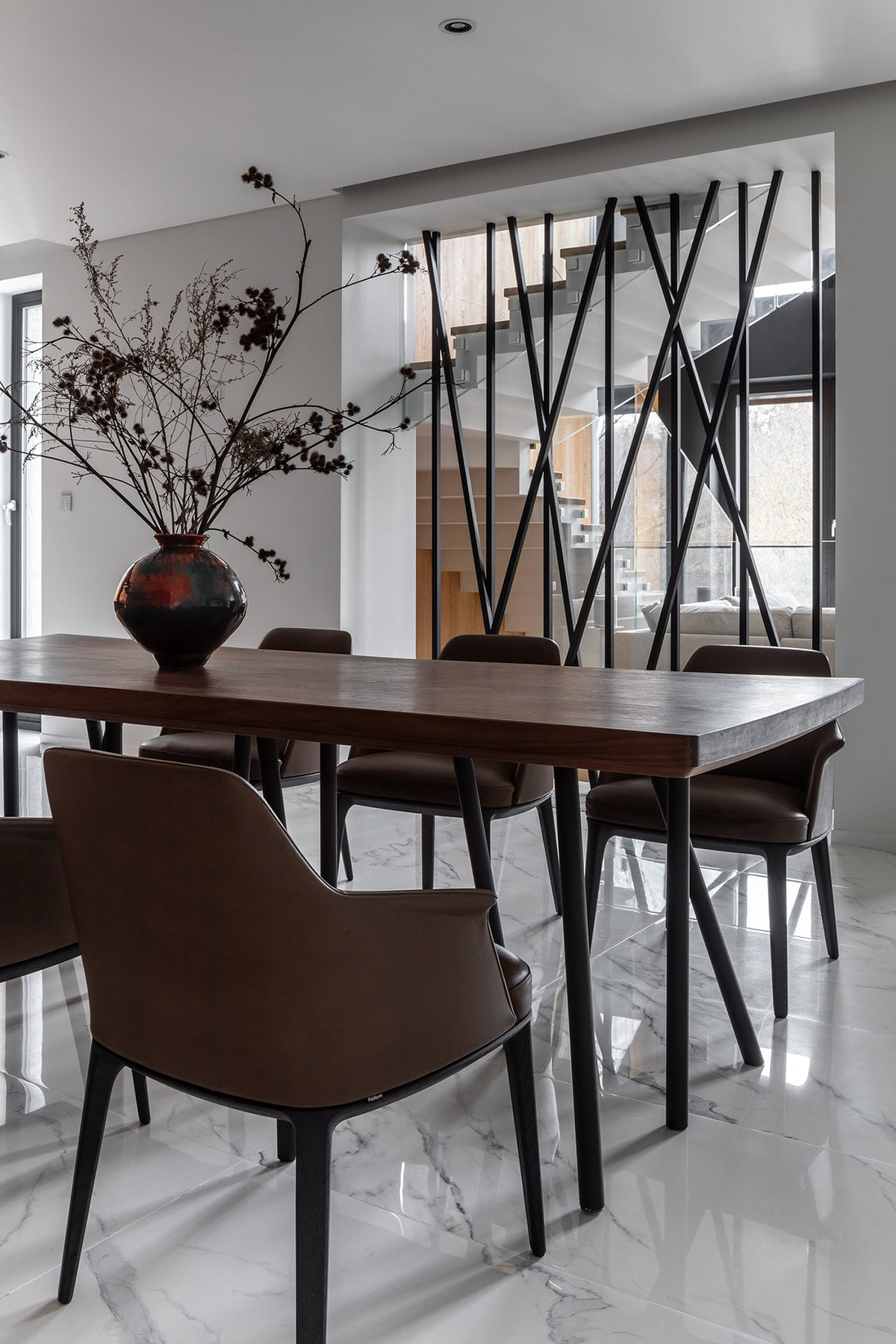 The lovely dining area is separated from the staircase with a decorative wall of thin black rods that still give a see-through view of the staircase.