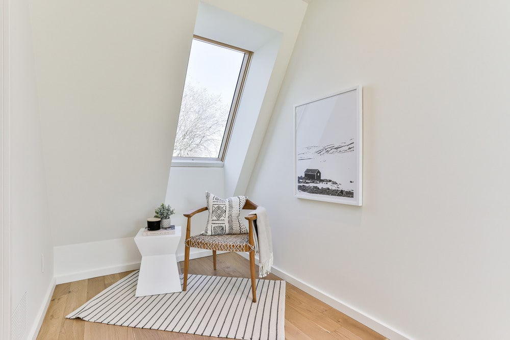 This is a charming reading nook at the corner of the bedroom with a wooden armchair, a small white side table and a large window to bring in natural lighting.