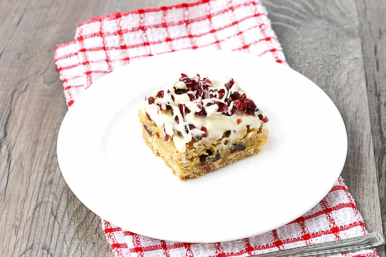 White chocolate cranberry brownies on a white round plate above a tablecloth.
