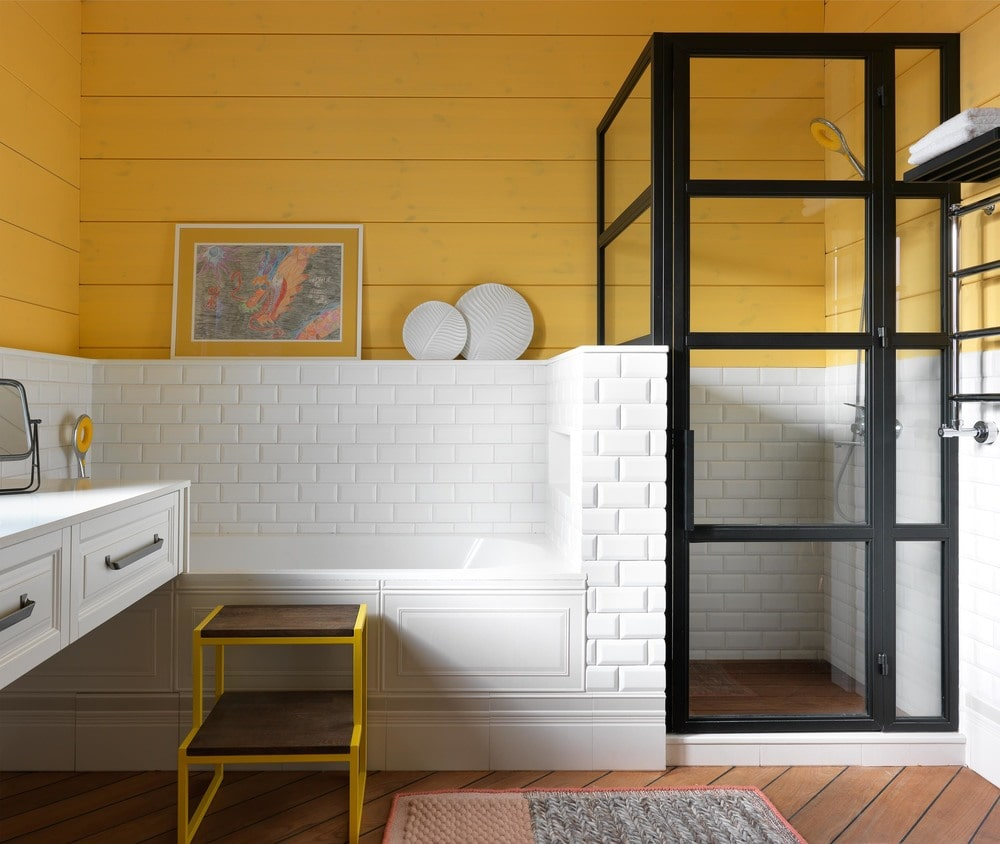 Beside the floating vanity is the bathtub inlaid at the corner with the same white backsplash that contrasts the black frames of the glass-enclosed walk-in shower.