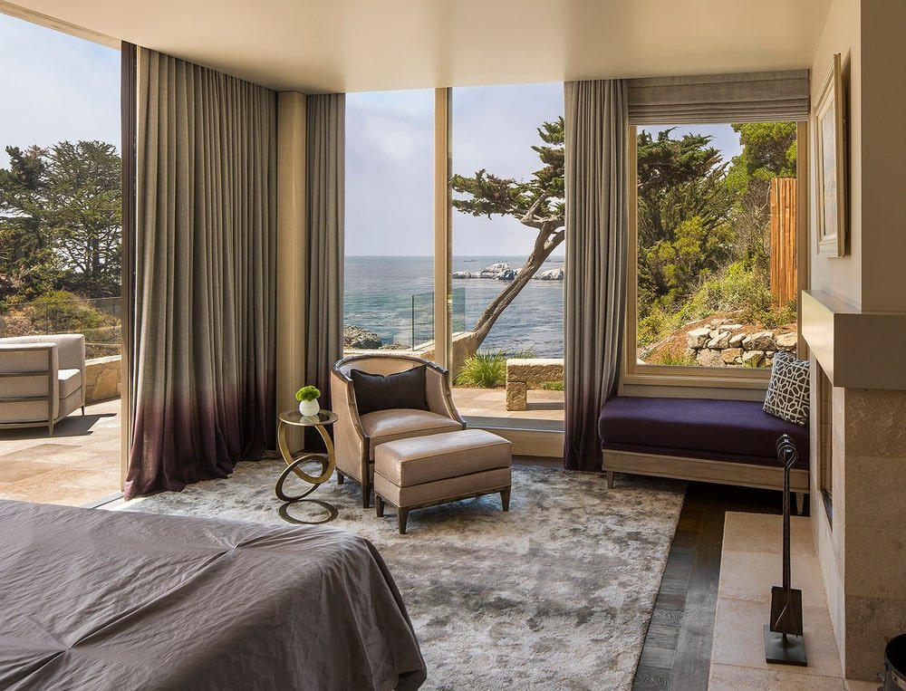 Across from the bed in this bedroom is a lovely beige armchair with its own footstool and a side table. This is placed by the tall glass walls and the large open wall with gray curtains.