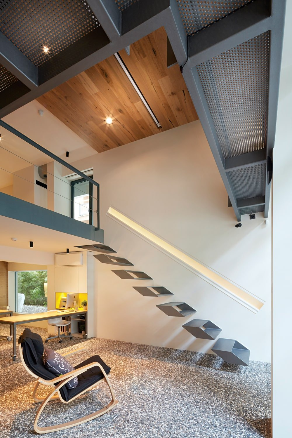 This lovely foyer has a tall wooden ceiling with recessed lights that complement the beige walls contrasted by the gray structures of the second level.