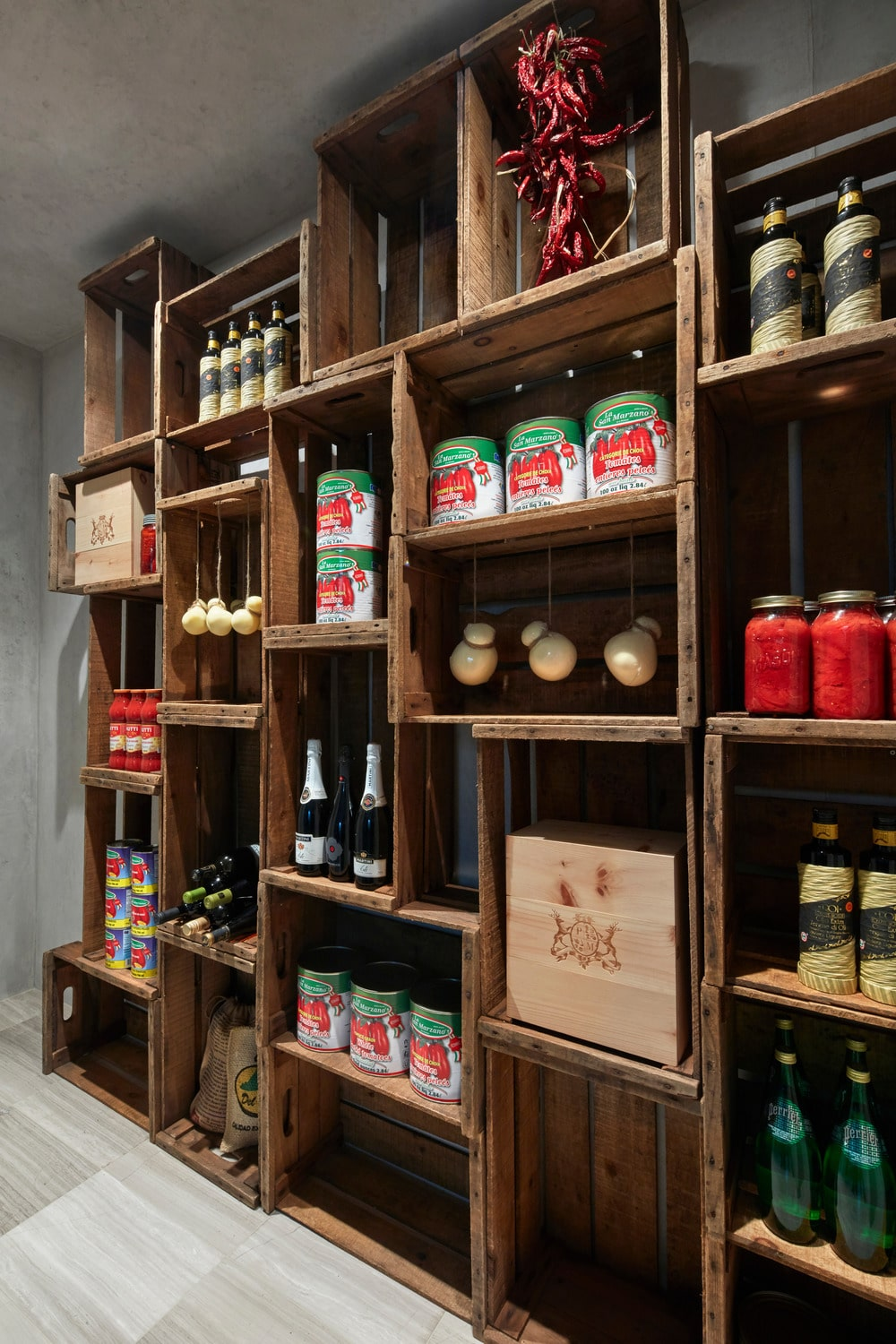 This is a close look at the pantry of the house with a large wooden structure that has a rustic look to its assembled wooden crates to form uneven shelves filled with various food products for storage.