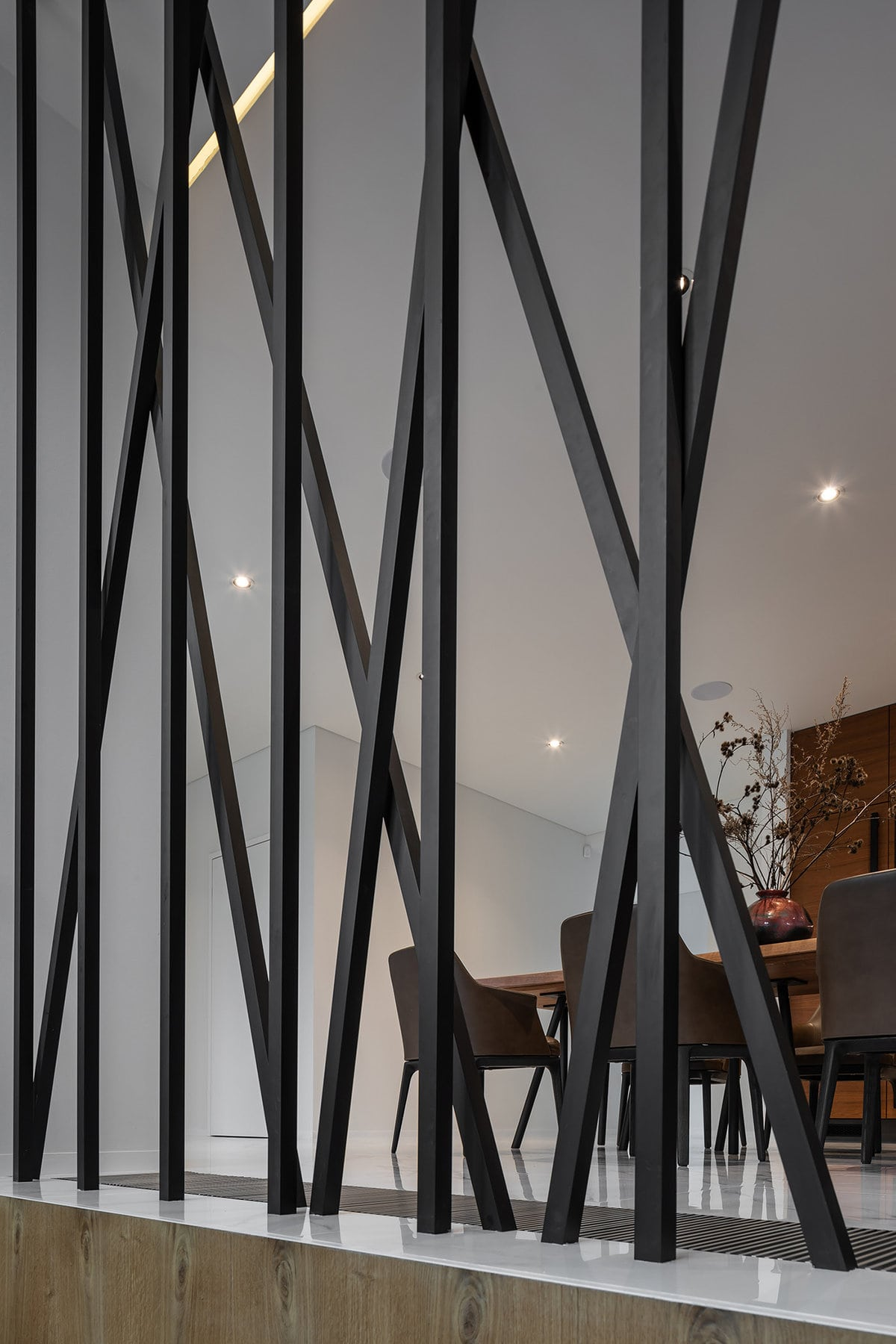 This is a close look at that decorative wall of thin black rods from the side of the staircase looking into the dining area.