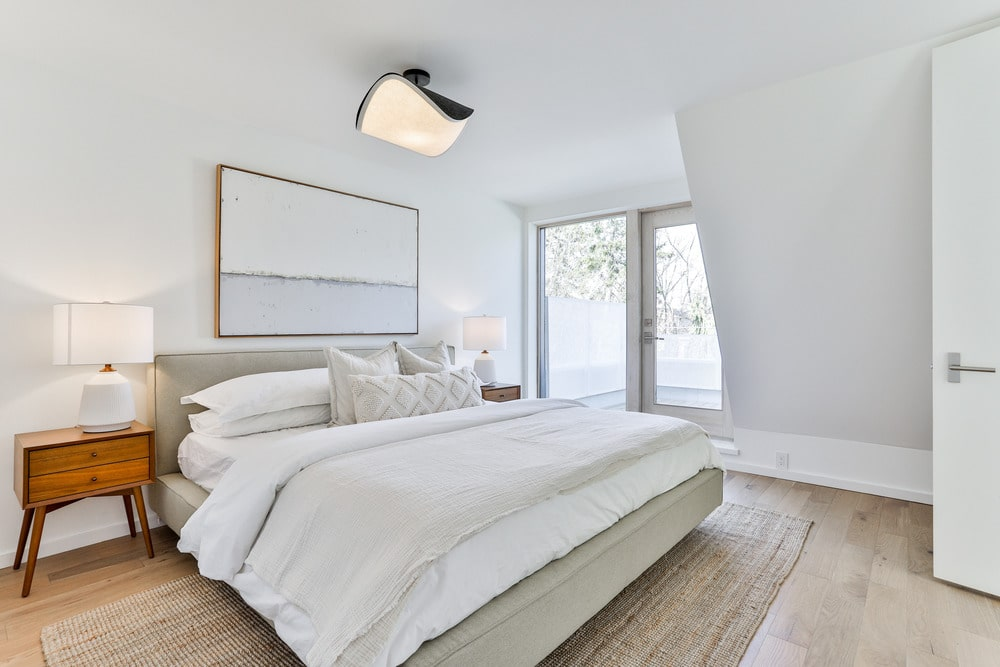 The master bedroom has a large cushioned gray bed with white sheets to match the walls and ceiling. On the far side, you can see the sliding glass doors that lead to the balcony.