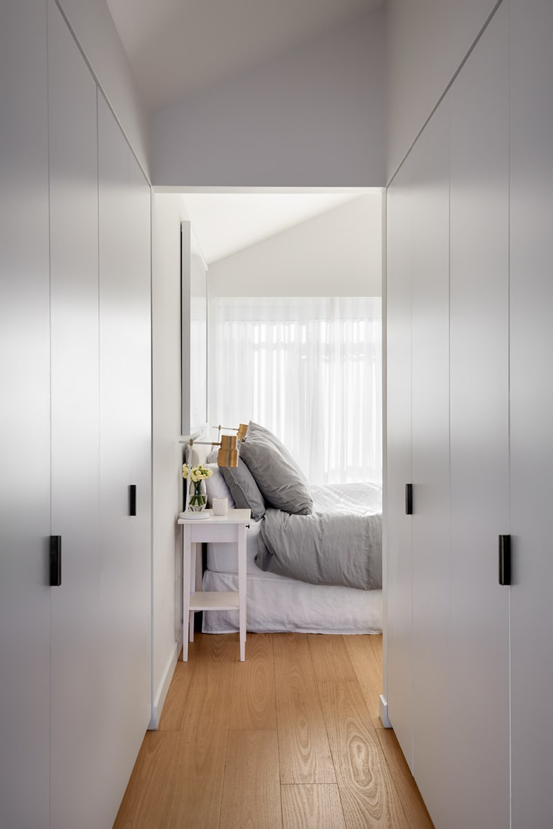 This is the walk-in closet of the bedroom with two sets of cabinets on each side of the long and narrow hardwood flooring that can lead back to the head of the bed.