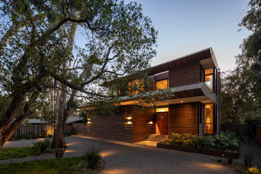 This is the front view of the charming house. Here you can see the lovely dark wooden exterior walls complemented by the warm outdoor lamps as well as the lovely landscaping.