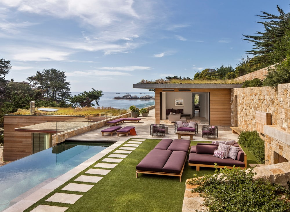 This is the backyard infinity pool with a concrete walkway on the side before transitioning to the grass lawn. This is where the outdoor daybeds are placed with comfortable cushions. These pair well with the cushions of the outdoor sofa set just a few steps away.