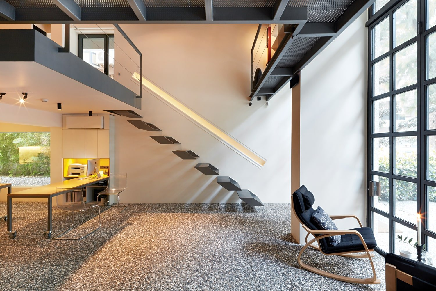 This is a lovely view of this studio loft with a modern floating staircase that matches with the steel structures of the second level. Here you can also see the large glass wall that rises from the floor to the next floor above.