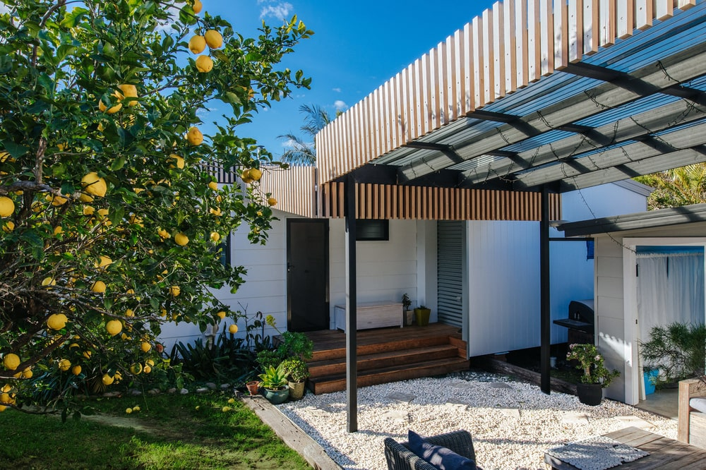 This side of the house also has a covered patio beside the beautiful lemon tree. This view also shows the black door that stands out against the white exterior walls.