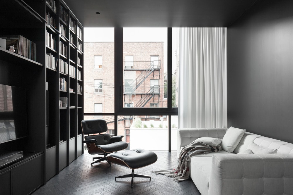 This is the gorgeous library with a large dark structure built onto the wall for the books. This is paired with a light gray sofa and an armchair with a footstool illuminated by the floor-to-ceiling glass wall.