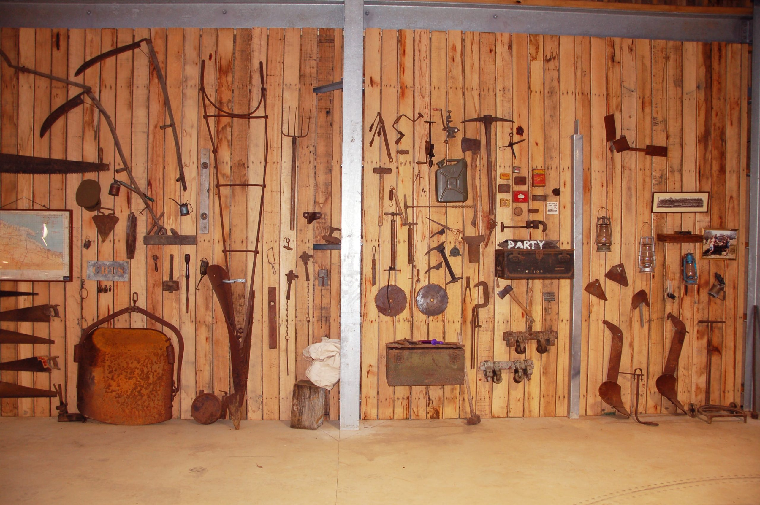 This is a closer look at the wall inside the garage and shed with various tools on display and storage.