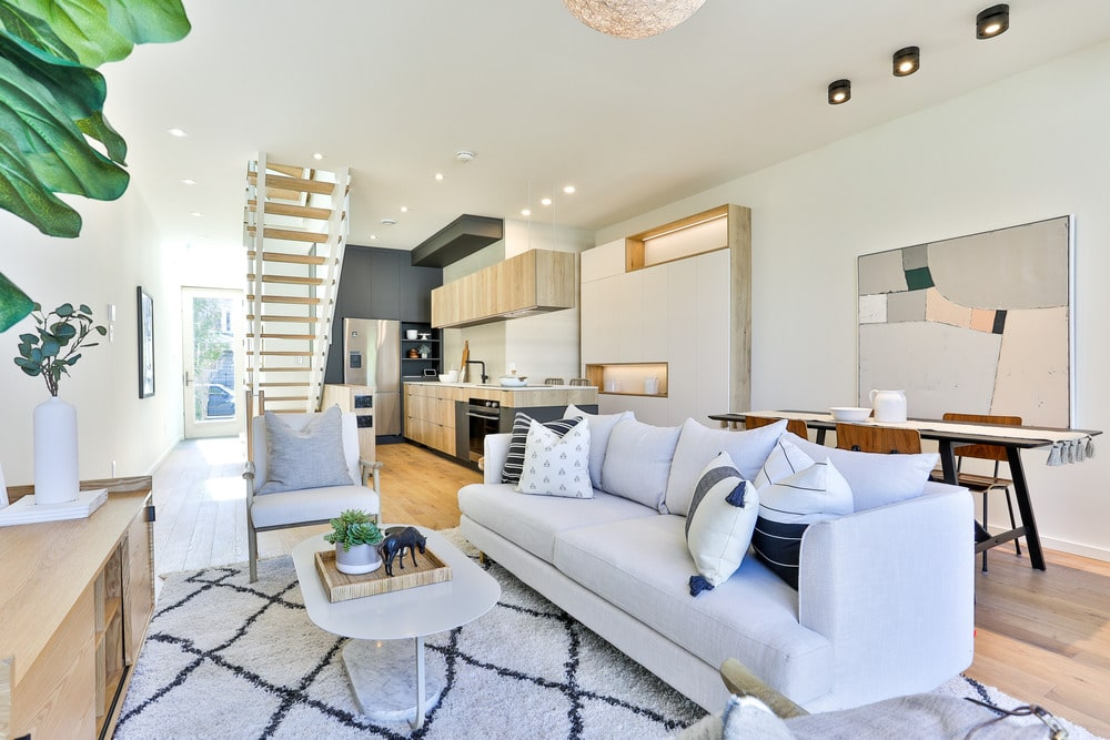 This is the great room that houses the living room, dining area and the kitchen within its white walls, white ceiling and light hardwood flooring.