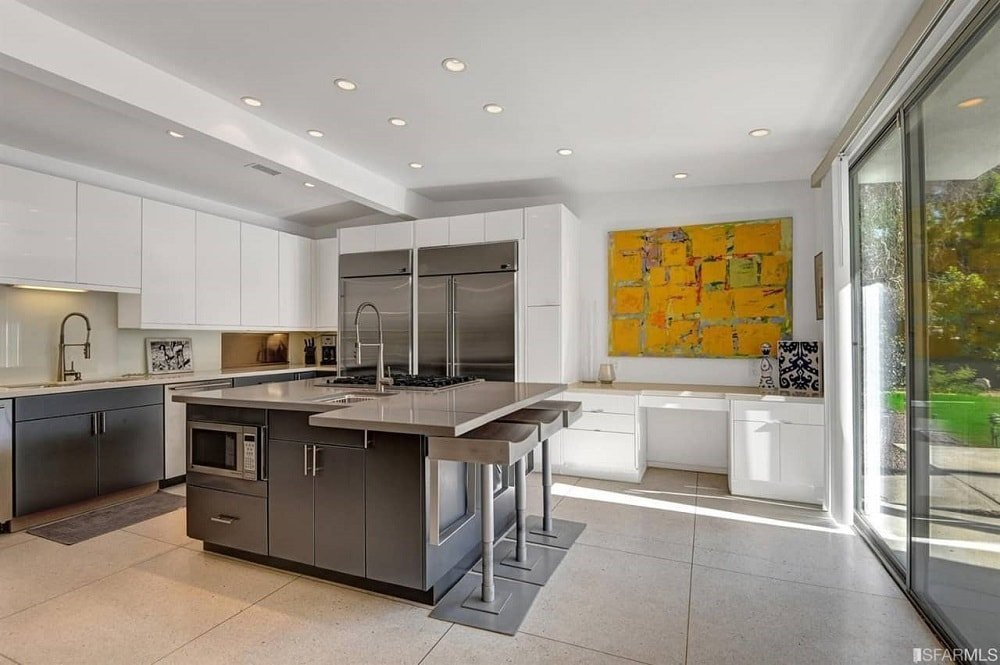 This is a mid-century modern kitchen with a large square gray kitchen island with a gray countertop that extends to the side for a built-in table. On the far wall is also a built-in white desk with drawers and topped with a colorful painting.