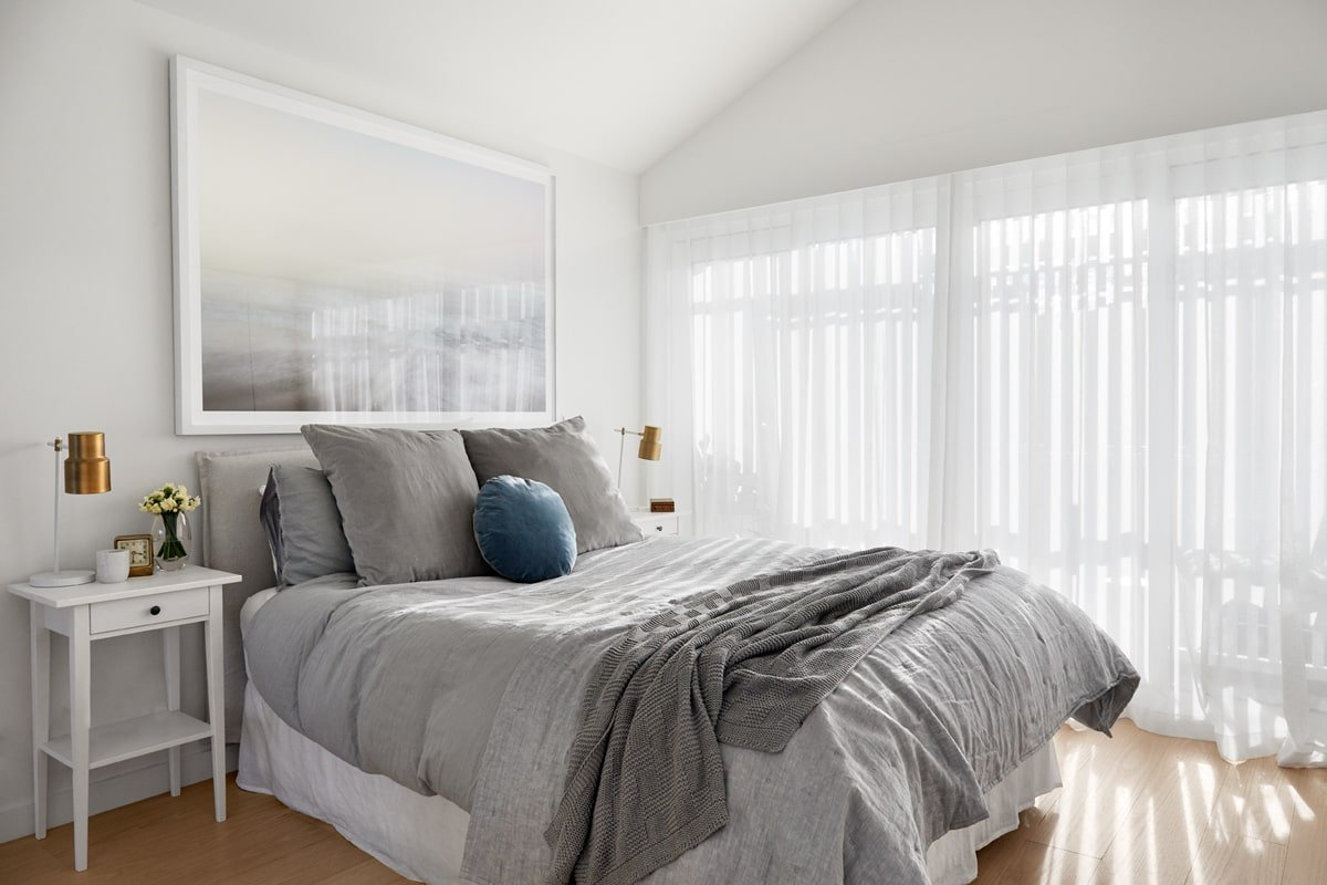 This bedroom has a large cushioned bed with gray sheets and pillows to give a soft contrast to the bright white walls and cathedral ceiling. These are all brightened by the natural lights filtered in through the sheer curtains of the balcony doors.