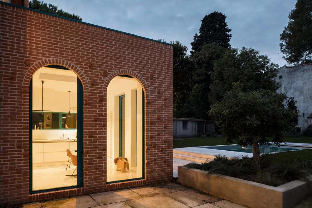 This nighttime look of the house shows its warm yellow glow that comes from the interior lighting. This pairs well with the brick exterior and the stone mosaic walkway.