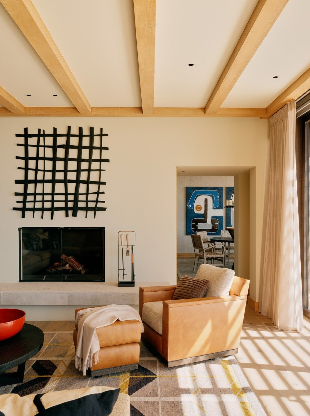 This is a living room a few steps from the dining room. It has a beige ceiling with exposed wooden beams that match well with the hue of the armchair beside the fireplace that stands out against the beige wall.