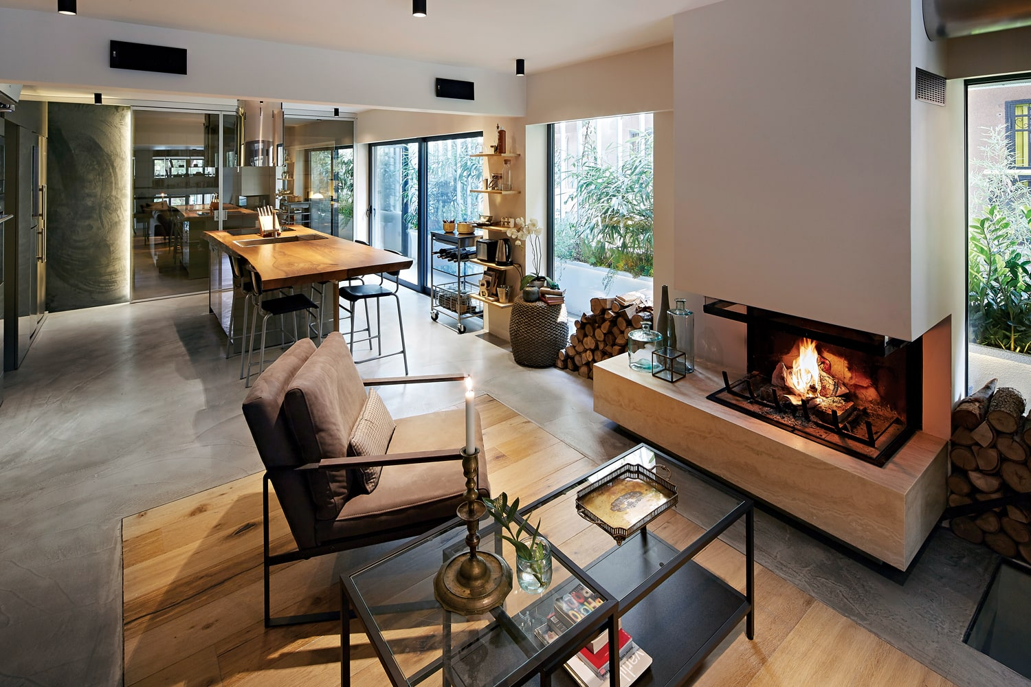 A close look at the living room shows that it has a couple of armchairs facing a modern fireplace embedded into the white wall beside the glass walls.