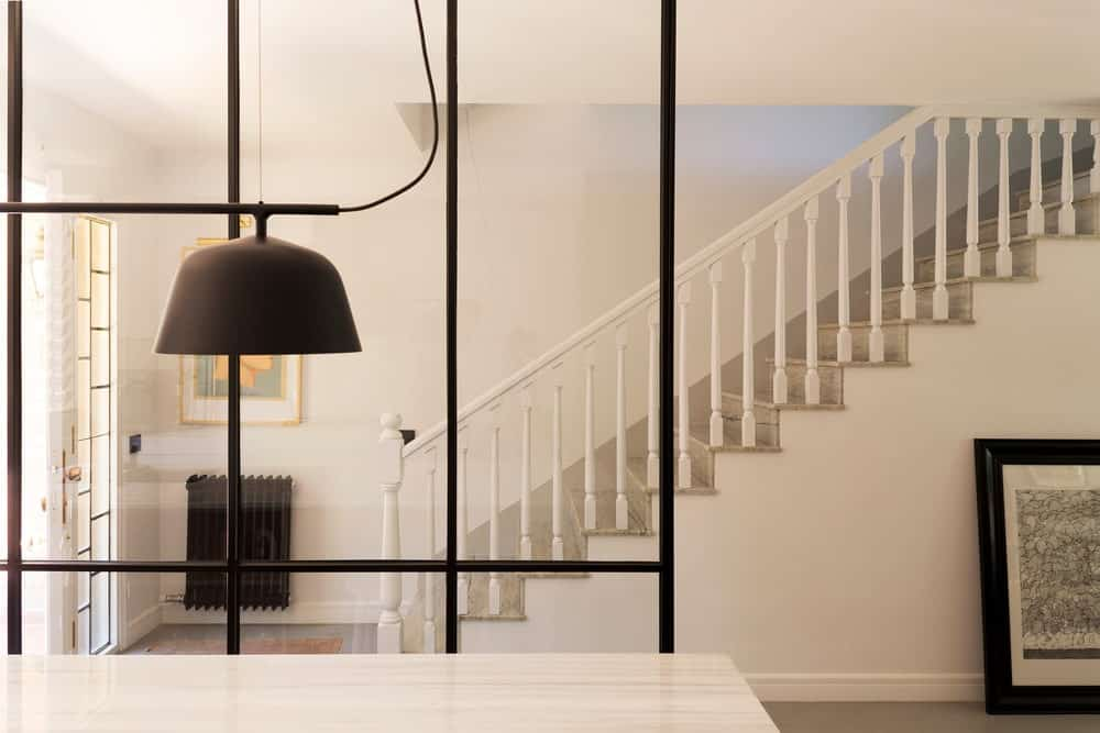 This is the simple and homey foyer. It has glass wall that separates it from the kitchen that has black frames to it. This matches with the black heater and the frame of the wall art on the side. These elements stand out against the white walls, ceiling and main door.