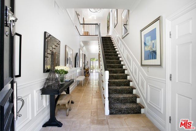 upon entry of the house, this foyer welcomes you with its bright white walls and ceiling to contrast the black carpeting of the staircase and the black console table on the left.