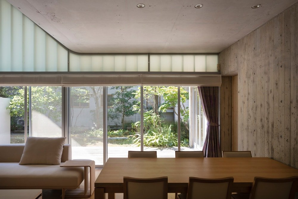 This is the view afforded by the large sliding glass doors from the vantage of the dining area beside the living room. This showcases the lush landscaping outside that gives a nice background for the neutral tones of the interior.