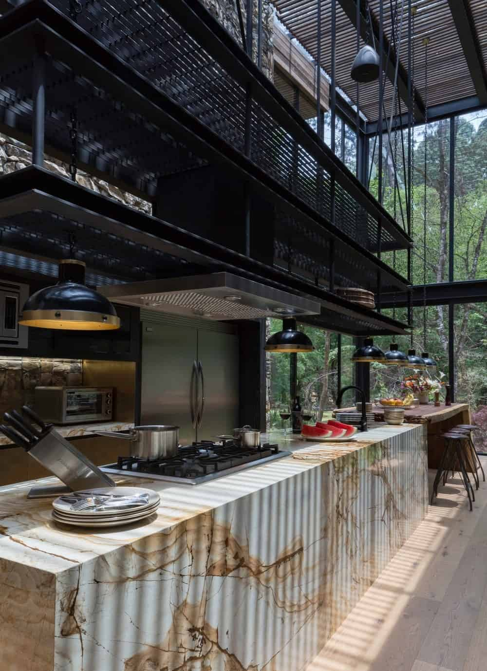 This is a long and narrow kitchen with a large marble waterfall kitchen island topped with metal rungs and has a built-in wooden table at the far end paired with wooden stools.