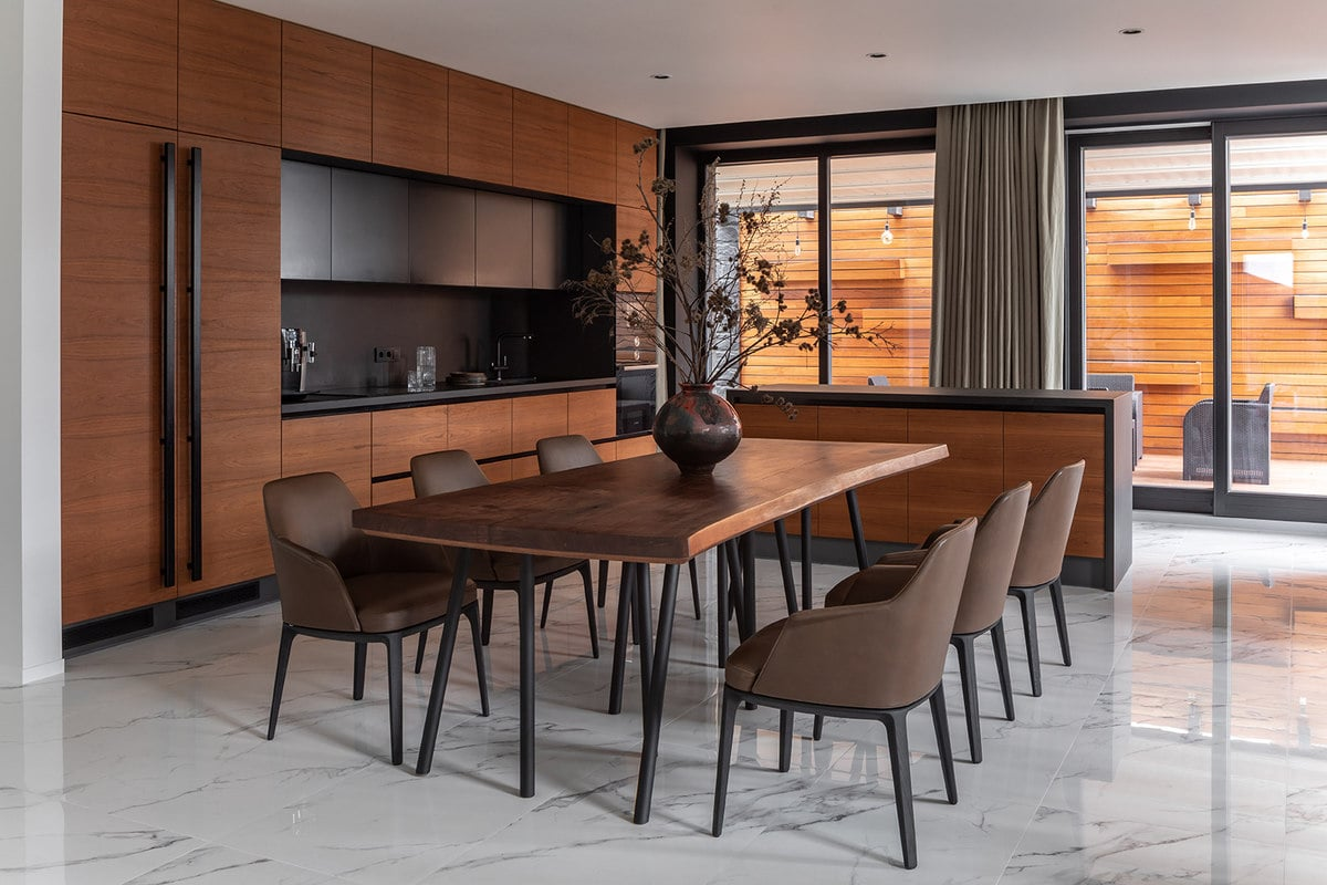 This is the gorgeous informal dining area with a large wooden dining table surrounded by brown cushioned chairs that match well with the brown wooden walls and cabinetry of the kitchen beside it.