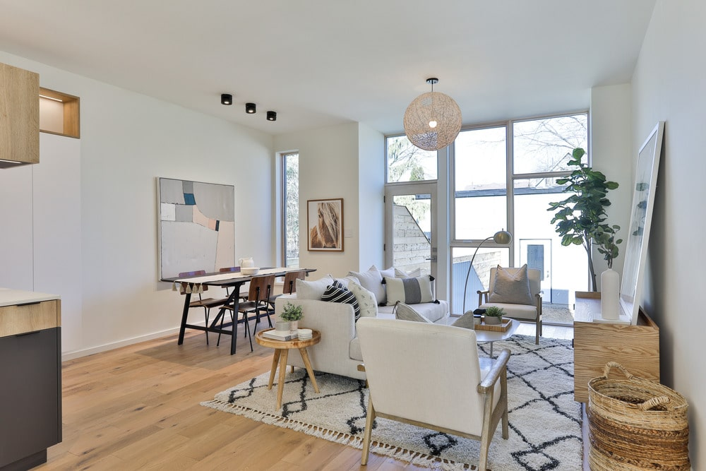 This view shows the living room and the dining area illuminated by the glass walls on the far side that brings in an abundance of natural lighting.