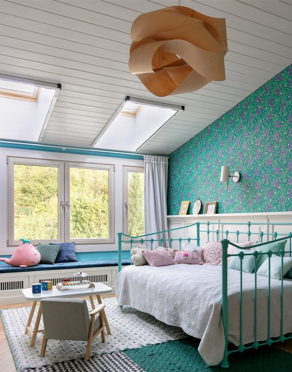 This is a gorgeous kid's bedroom with a lovely green wallpaper that matches the green railings of the bed. The bedroom has enough space for a play area and a reading nook by the window.
