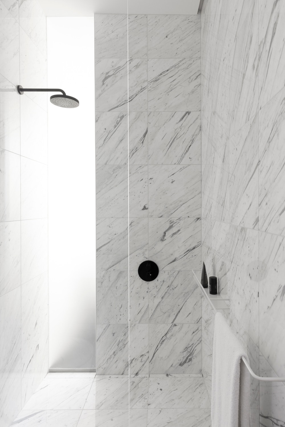 This is a close look at the shower area that has frosted glass and white marble walls that makes the black fixtures stand out.