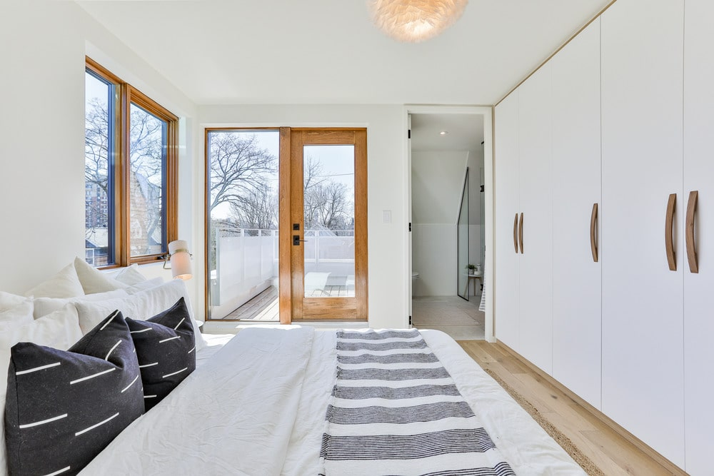 The simple white bed with black pillows. This bed blends quite well with the white walls and white ceiling that has a beige light in the middle. The wooden structure across from the bed has built-in cabinets.