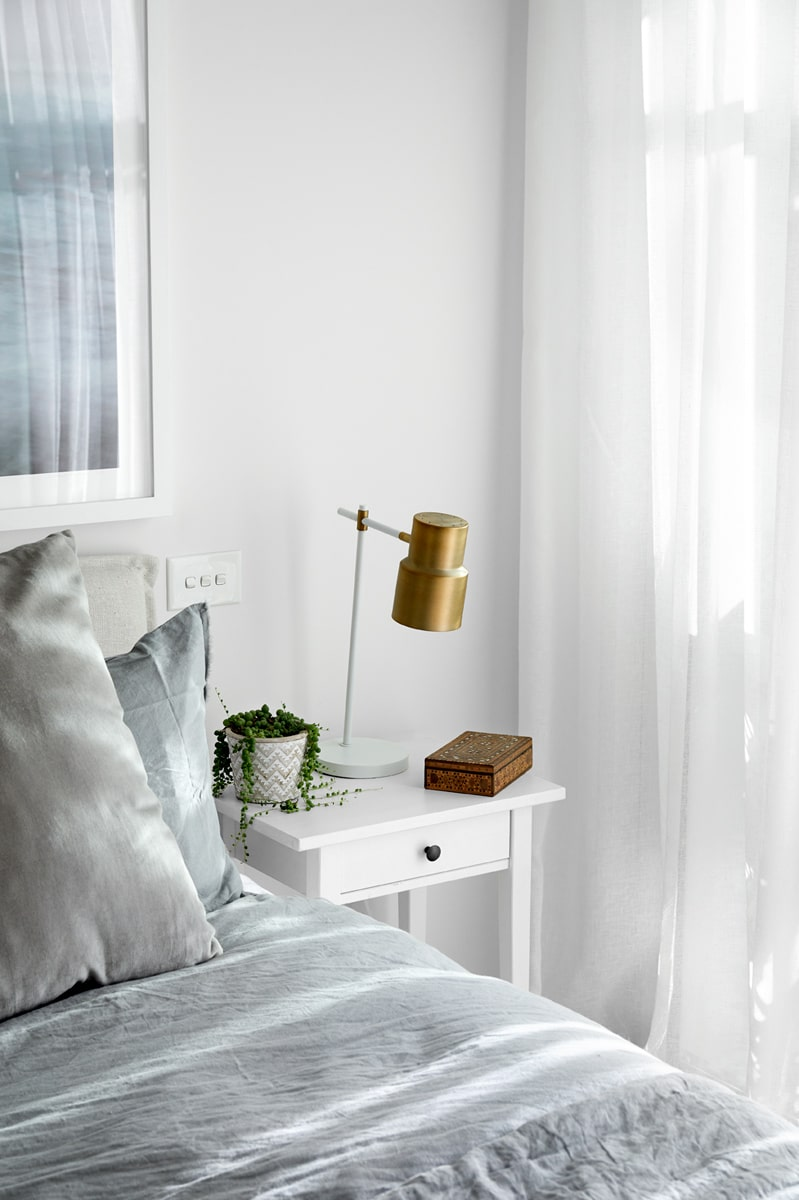 A closer look at the bedroom showcases the gorgeous small white bedside tables with a small built-in drawer. There is also a table lamp on the bedside table with a brass hue to it.