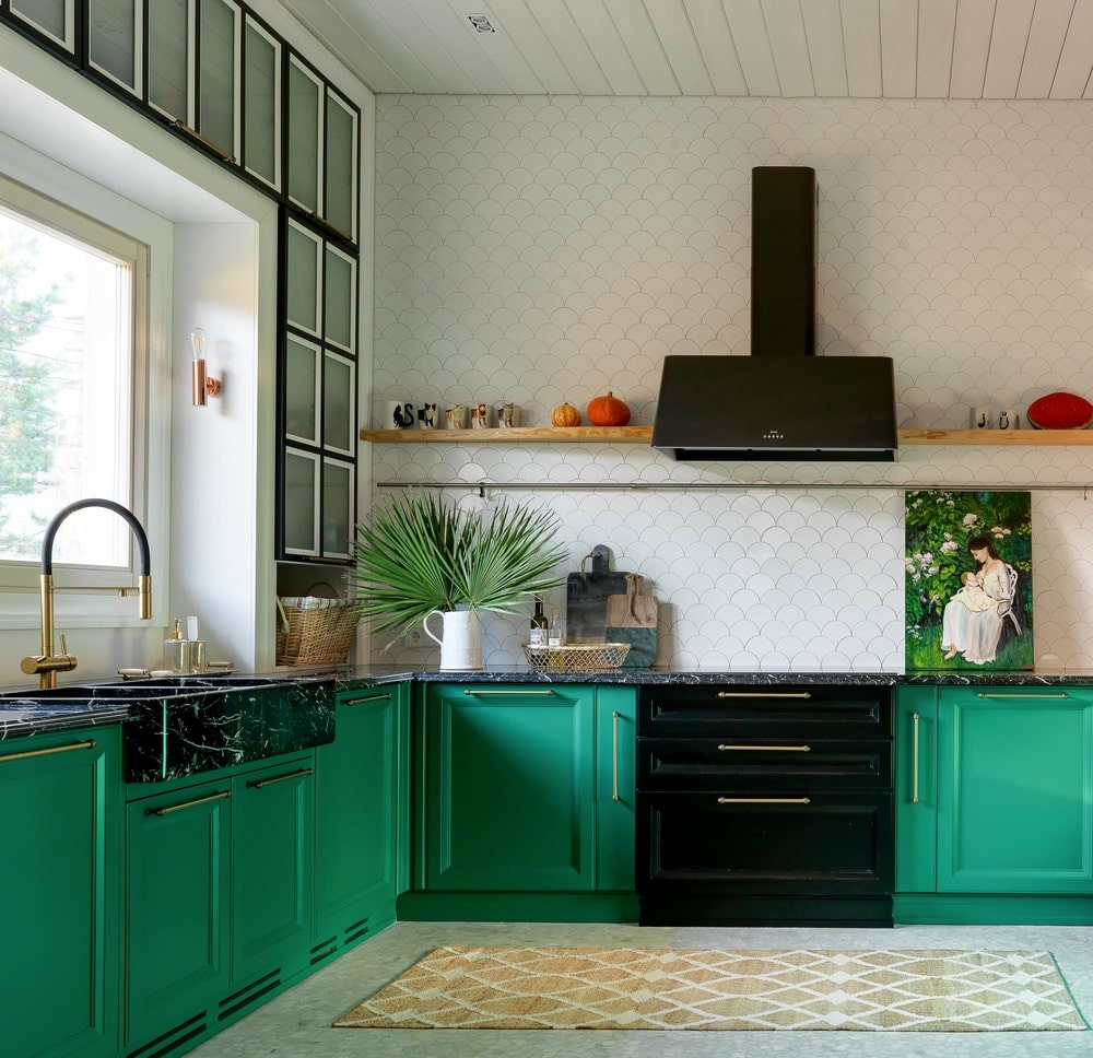 The kitchen has lovely green cabinetry lining the white walls. These are contrasted by the black stove-top oven with a matching pitch black vent just above the cooking area.