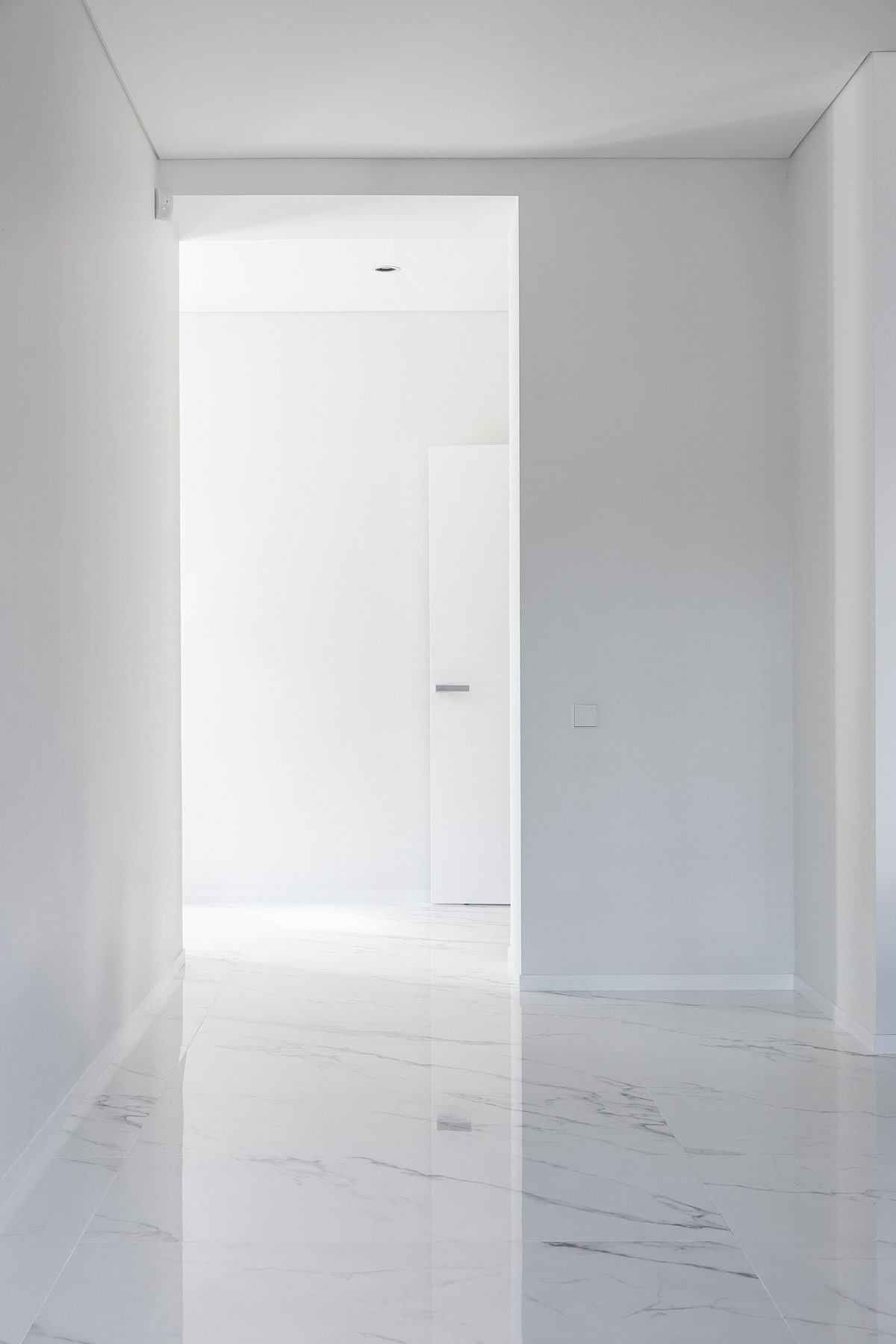 This is a bright hallway with white walls, white ceiling and white doors. These are then complemented by the white marble flooring.