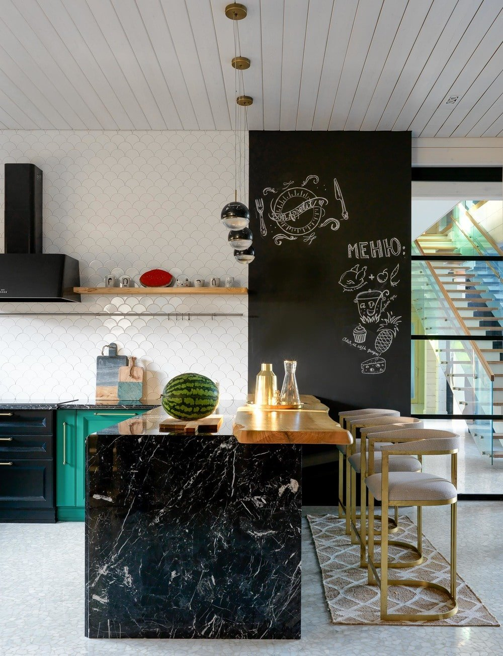 The cabinetry extends and forms a peninsula with a black marble surface to match the black wall on the side of the breakfast bar making the beige modern stools stand out.