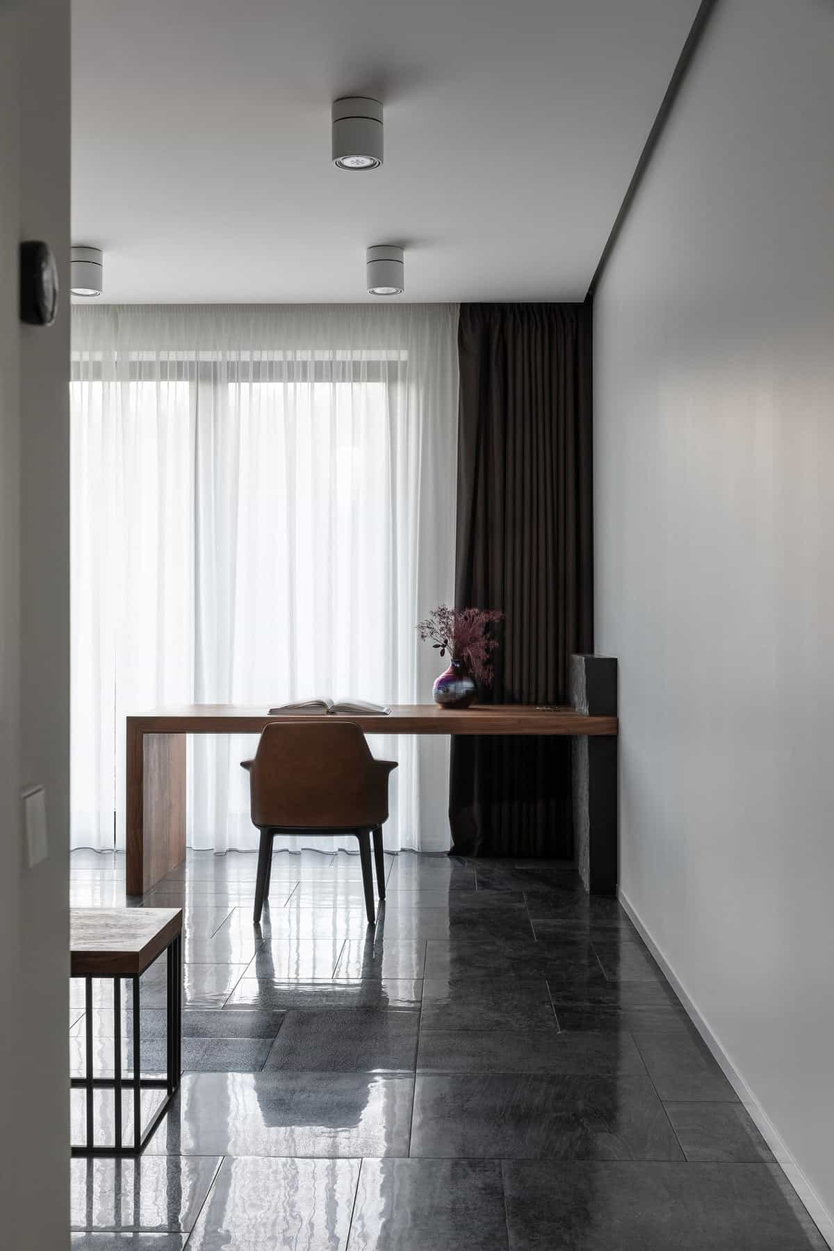 This is a simple corner office with white walls and white ceiling illuminated by the curtained glass wall. This makes the contrast with the black flooring tiles and the black curtain along with the support of the built-in desk.