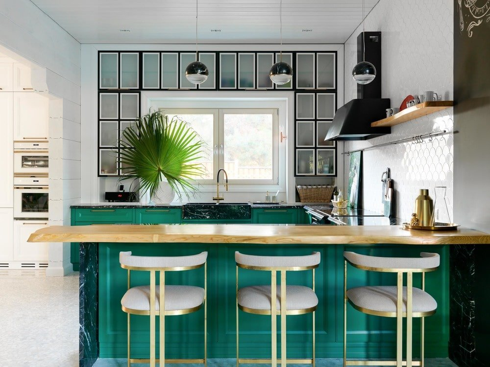 This is a closer look at the breakfast bar of the peninsula with a second-tier countertop made of thick wood. The beige modern stools also stand out against the green tone of the peninsula side.