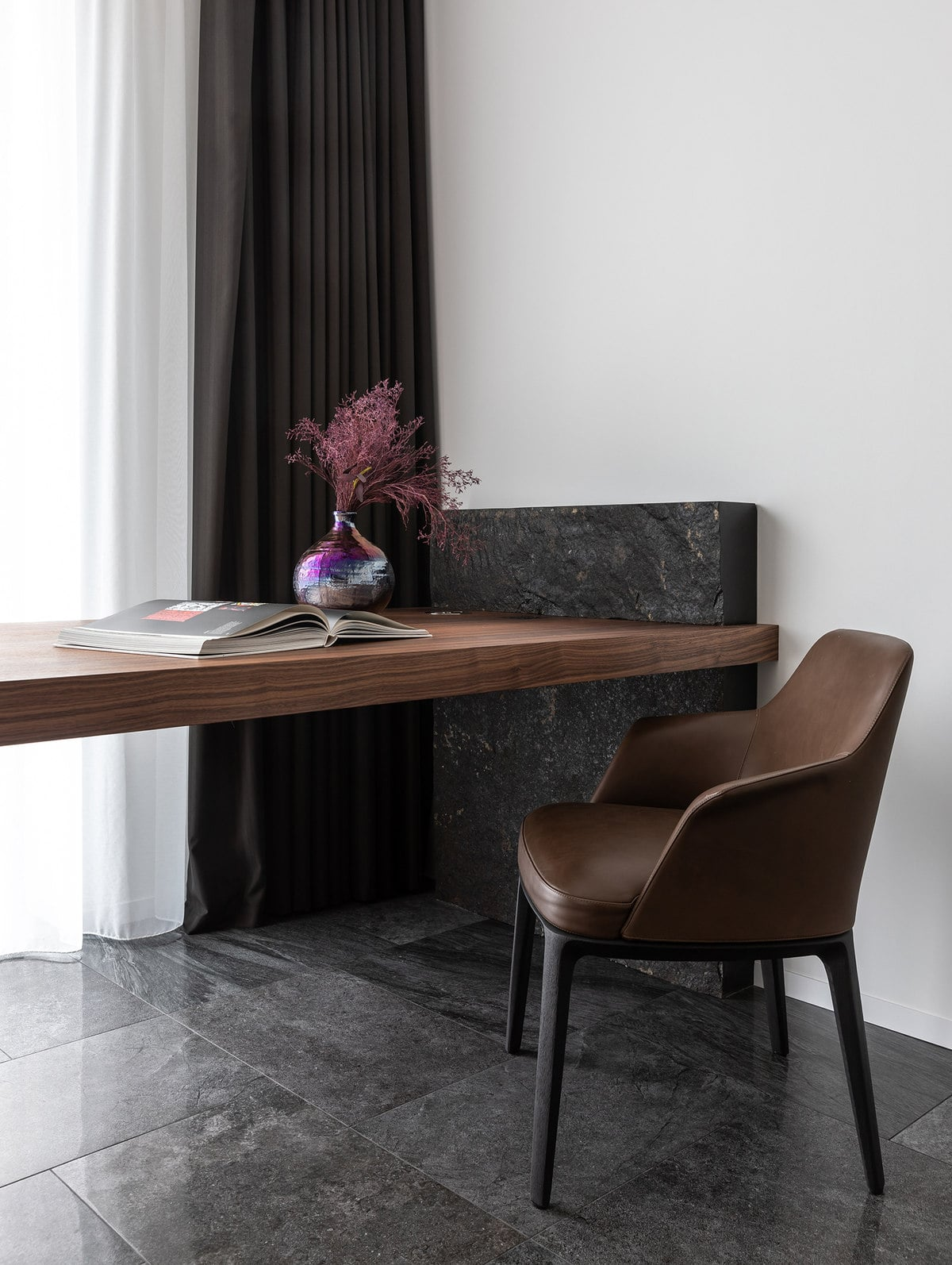 This close look at the office gives us a look at the built-in wooden desk supported by a black marble panel that blends perfectly with the flooring but contrasts the white wall.
