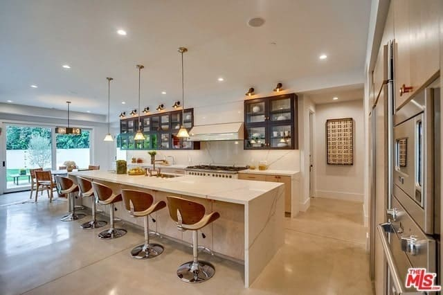 This long and narrow kitchen has modern white waterfal countertops to match the backsplash and ceiling that has pendant lights over the kitchen island.