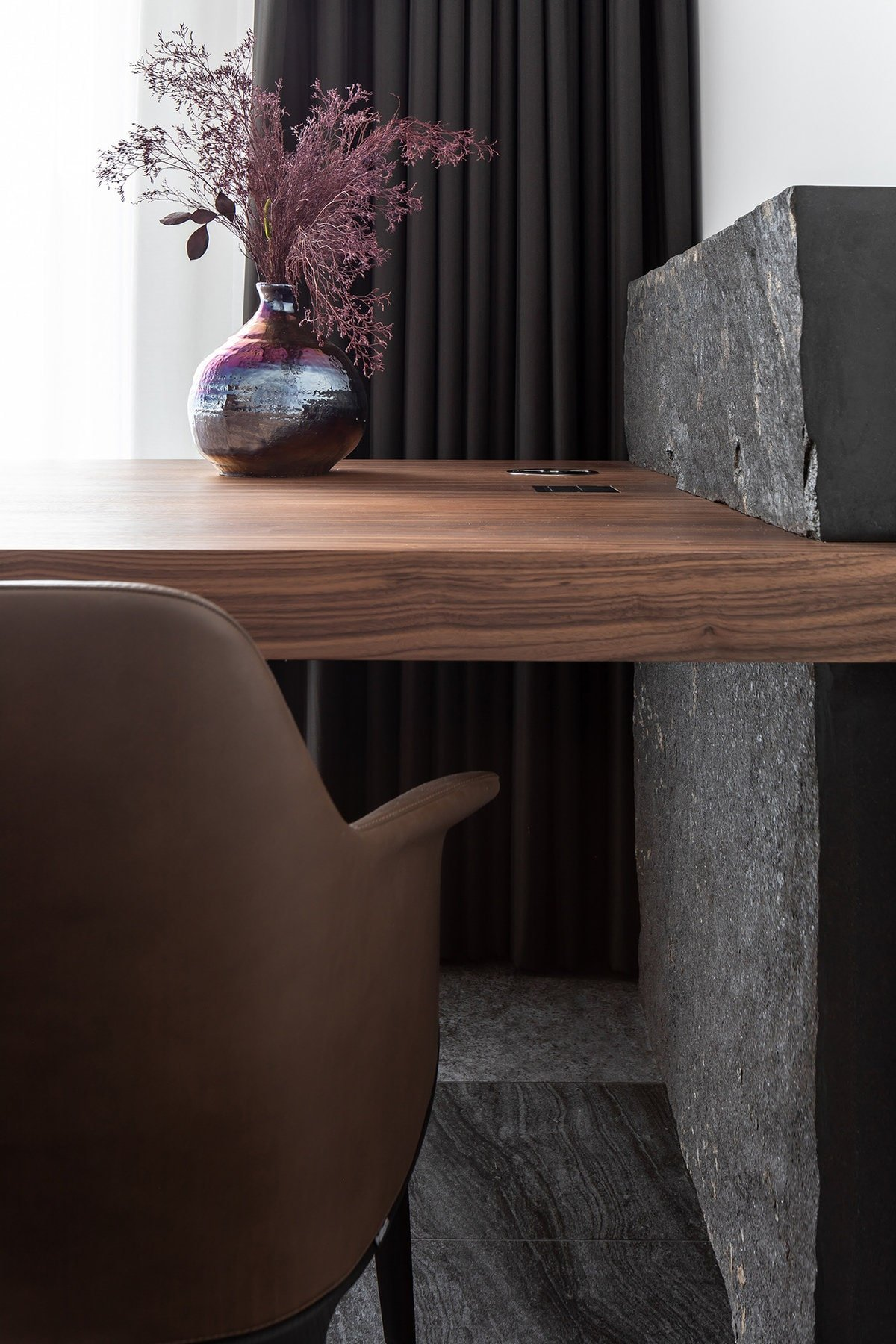 A close inspection of the corner shows more of the black marble stone panel that supports the wooden desk. This also shows the dark curtains that can close to eliminate the natural lighting completely.