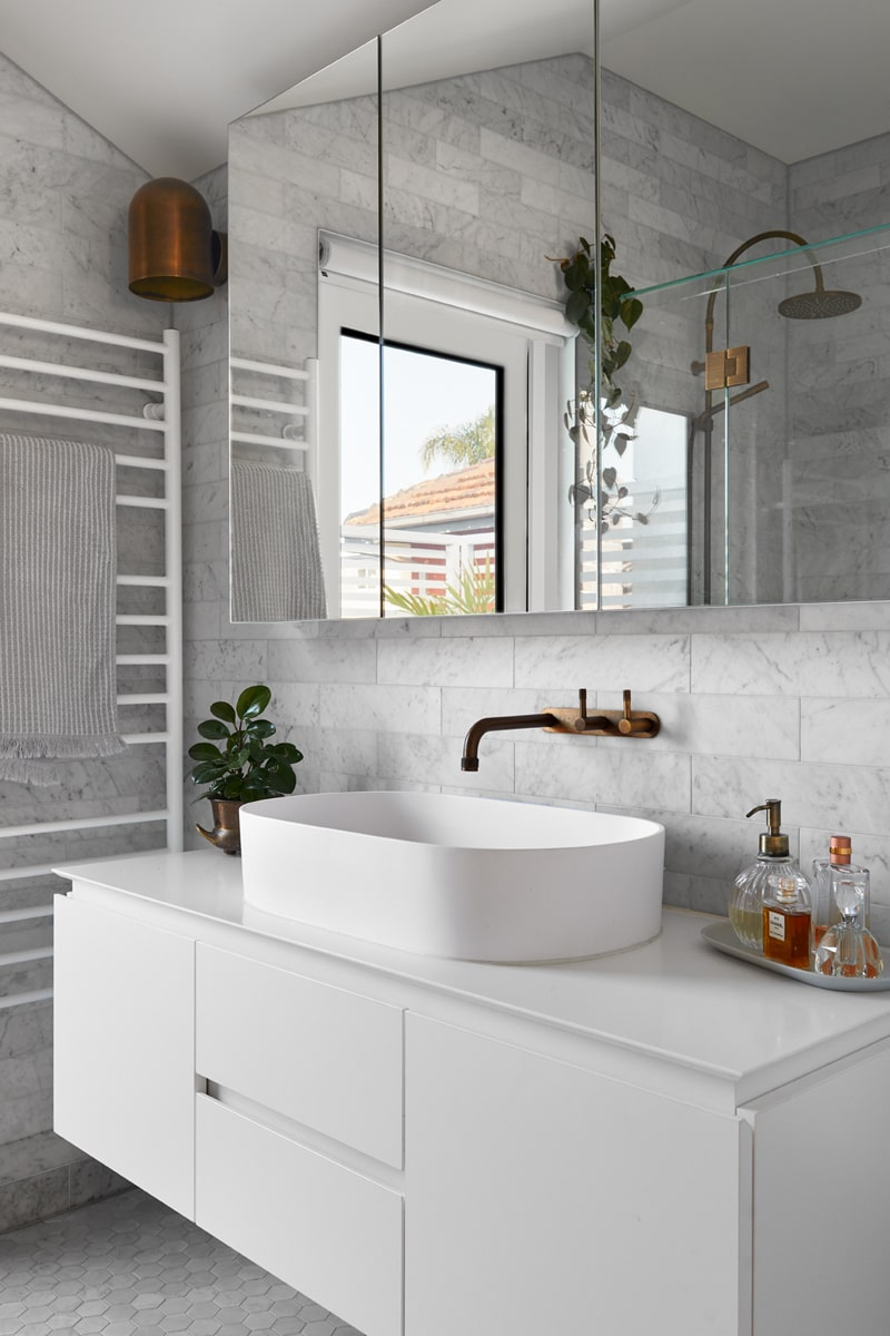 This other bathroom has a modern white vanity that blends well with the white countertop and white porcelain bowl sink. This is topped with a brass faucet and a large wall-mounted mirror.