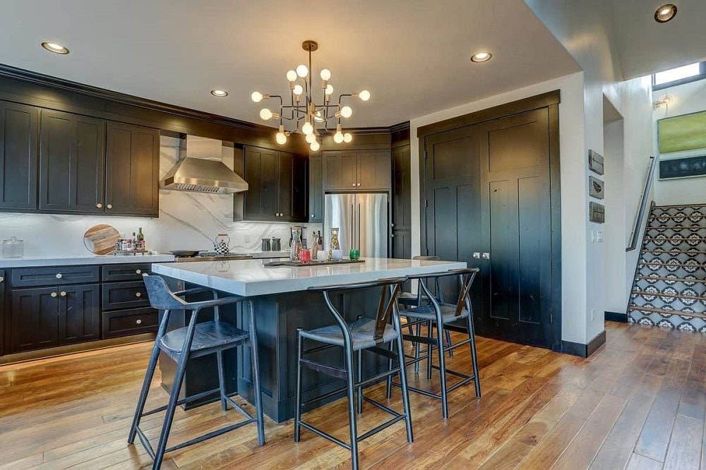 The kitchen is dominated by a lovely decorative chandelier that hangs over the large kitchen island in the middle of the hardwood flooring. This has a built-in table paired with metal stools.