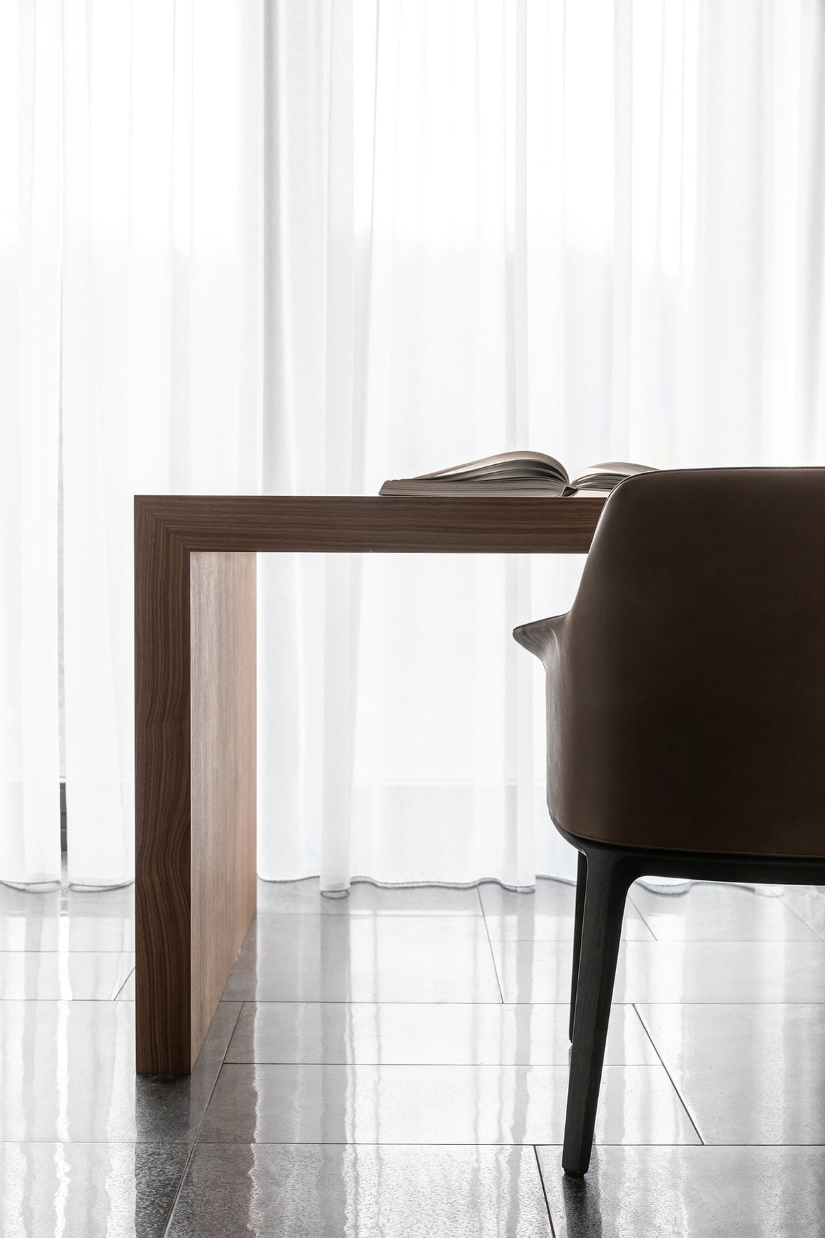 This waterfall built-in wooden desk is paired with a brown leather chair with comfortable armrests.