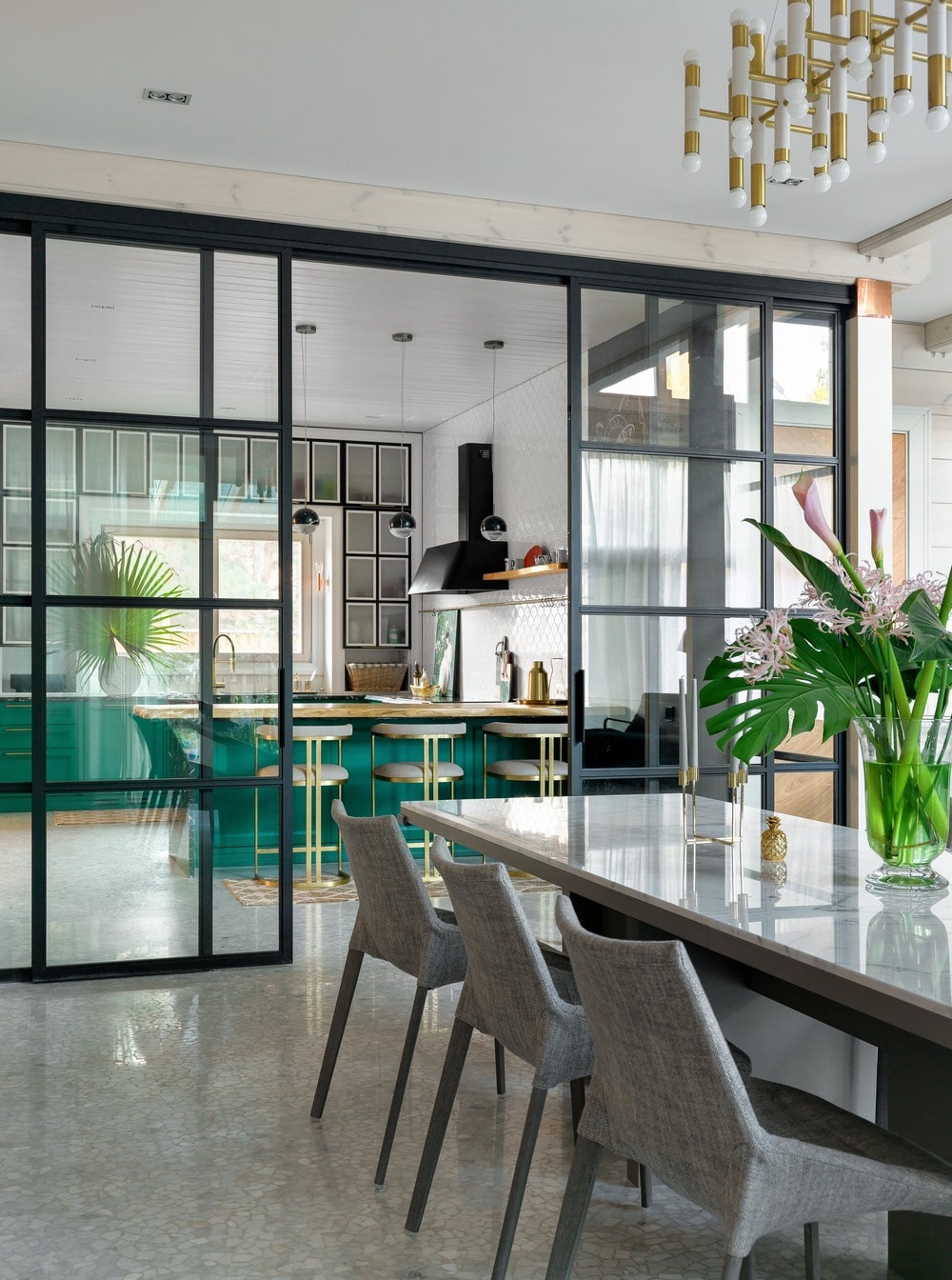 The kitchen is separated from the dining area with a set of floor-to-ceiling French sliding glass doors with black frames to stand out against the walls and flooring.