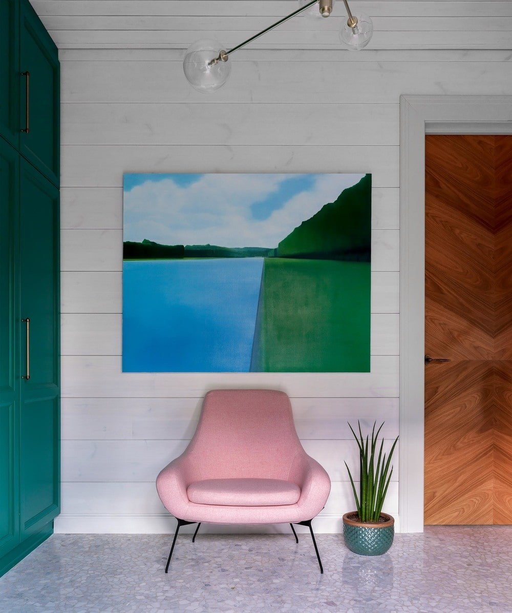 Beside the cabinet is a lovely pink cushioned armchair adorned with a colorful painting above it and a small potted plant on the side.