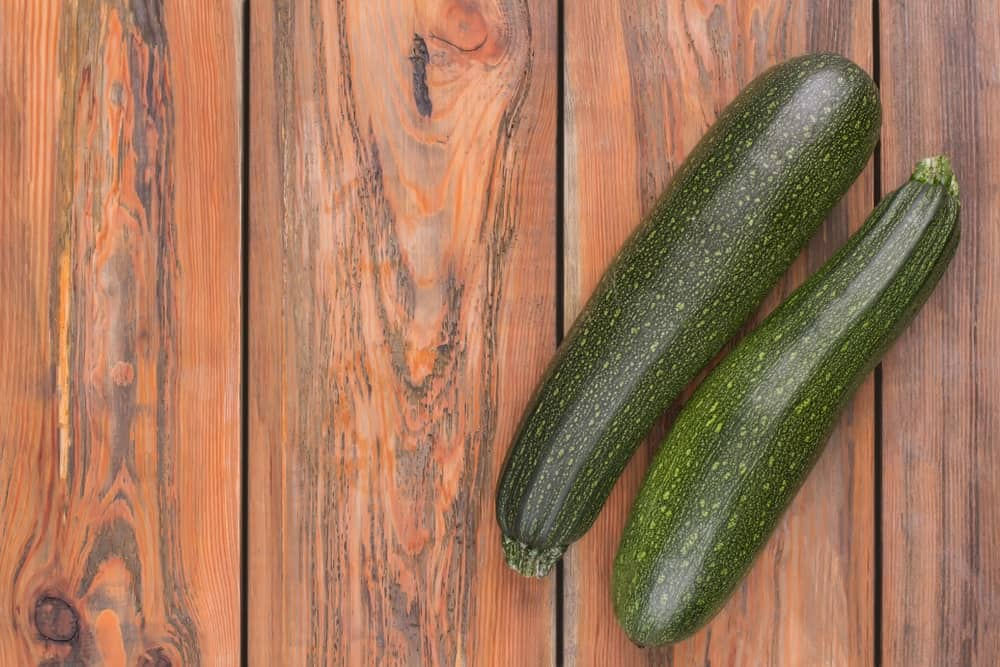 A pair of black beauty zucchinis on a wooden surface.