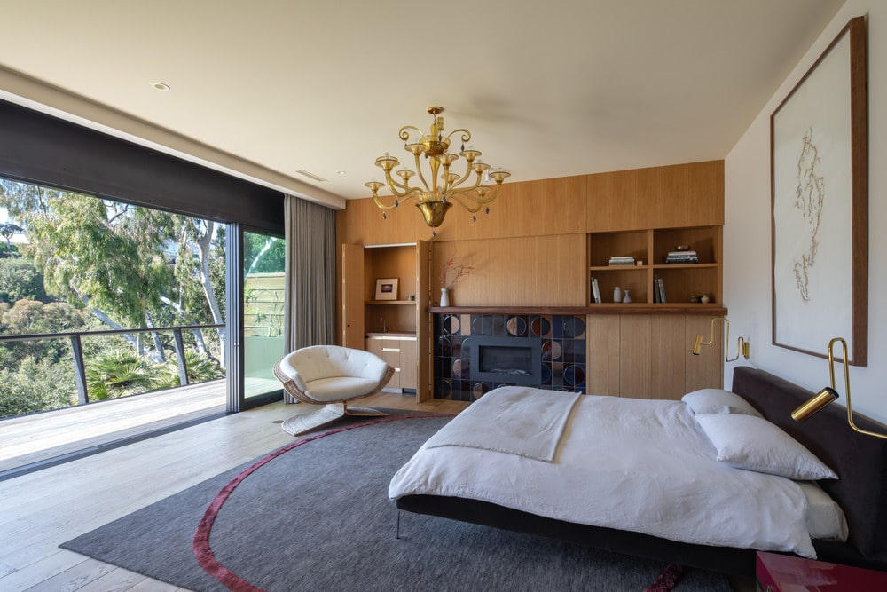 The primary bedroom has a large floating bed with white sheets to make it stand out against the gray area rug topped with a golden chandelier. On the side of the bed is a large wooden structure that has built-in cabinets, shelves and fireplace.